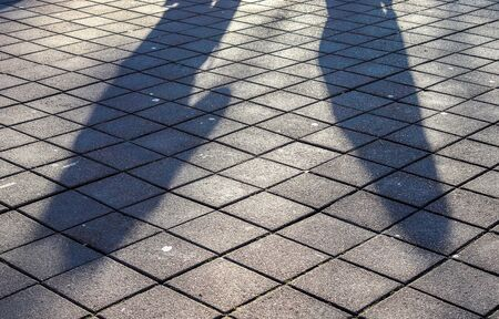 Shadows of people in a shopping area on a cobblestone ground 写真素材