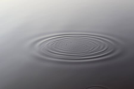 Detailed close up view on water surfaces with waves and ripples and the sunlight reflecting at the surface