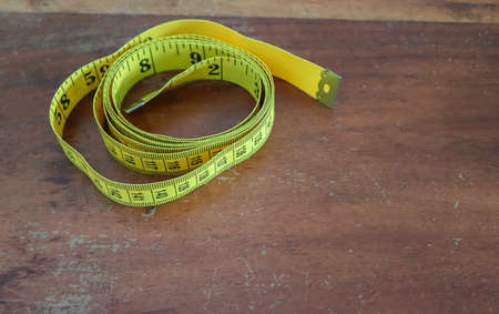Yellow tape measure isolated on a brown wooden background. Sewing concept.