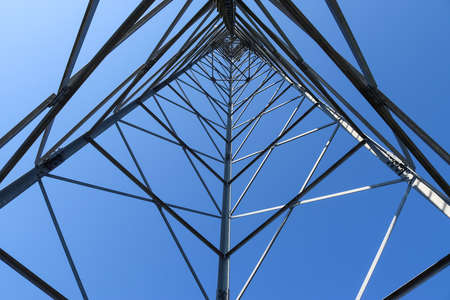 Electric antenna and communication transmitter tower in a european landscape against a blue sky