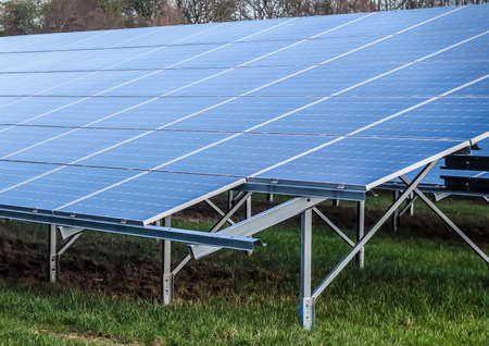 Generating clean energy with solar modules in a big park in northern Europe. 免版税图像