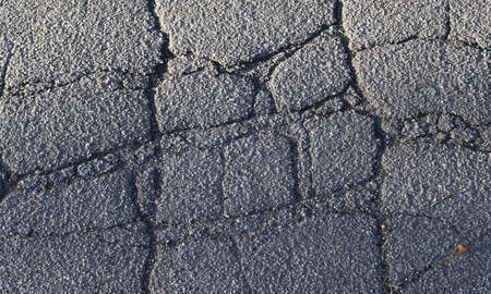 Detailed view on asphalt surfaces of different streets and roads with cracks in a close up