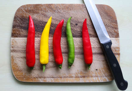 Top and perspective view of chili pepper and knife on a wooden cutting board with an isolated background