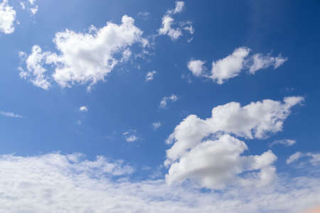 Beautiful fluffy white beautiful cloud formations in a deep blue summer sky