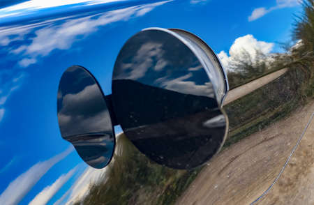Reflections of a blue sky with clouds in the surface of a black sports car