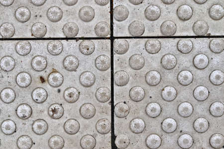 Detailed close up texture on structured floor tiles on a ground