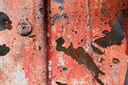 Detailed and colorful close up at cracked and peeling paint on concrete wall textures in high resolution.