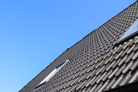 Roof window in velux style with black roof tiles
