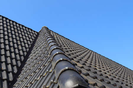 Roof window in velux style with black roof tiles Standard-Bild