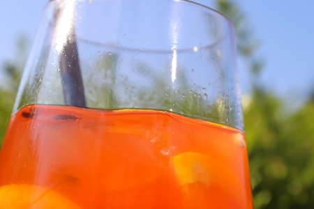Refreshing orange summer cocktails with ice against a blue sky background.