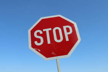 Close up of a stop sign against a clear blue sky