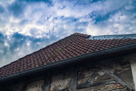 Old roof with black roof tiles with half timebered walls