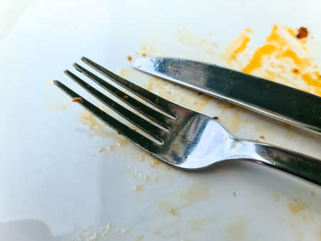 Used empty white plate with fork and knife