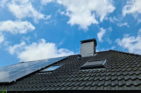 Solar panels producing clean energy on a roof of a residential house