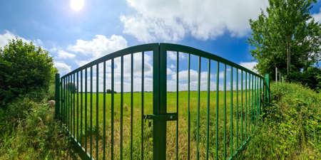 Big green metal gate to a field