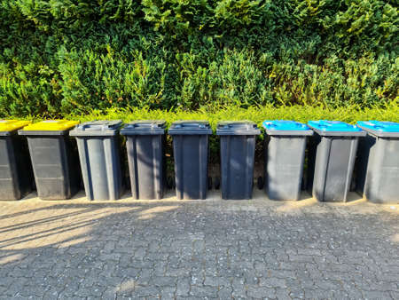 Lots of garbage cans standing in a row