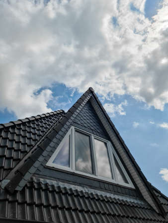 Open roof window in velux style with surrounding black roof tiles