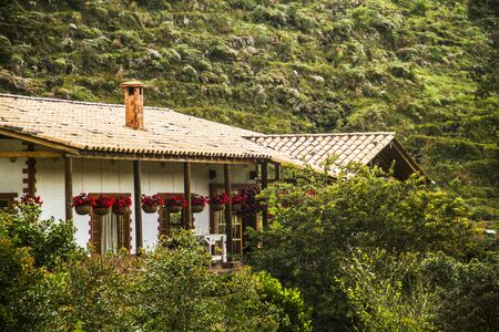 Colonial House between green mountains with red flowers in Antioquia Colombia. Traditional housing in the countryside.
