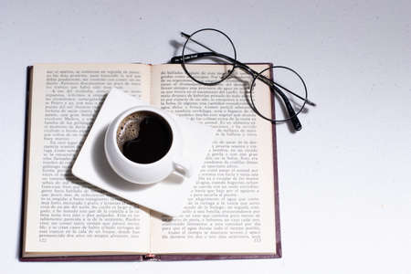 white cup with Colombian coffee on a book and round glasses