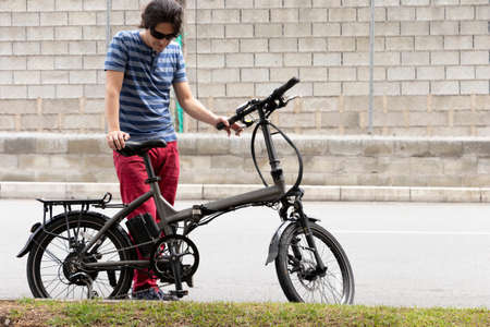 Man in blue striped shirt and red pants on the side of the road in the city with electric bike
