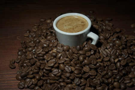 Cup of coffee surrounded by coffee beans Stock Photo