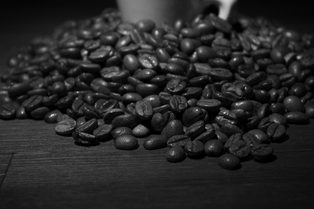 Black and white coffee beans at wooden table