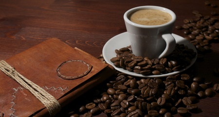 Coffee beans at wooden table with espresso cup and old leather book