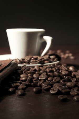 Coffee beans at wooden table with espresso cup