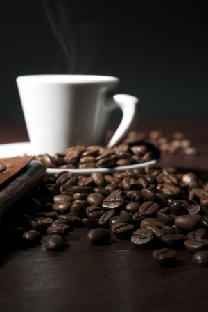 Coffee beans at wooden table with hot espresso cup  Stock Photo