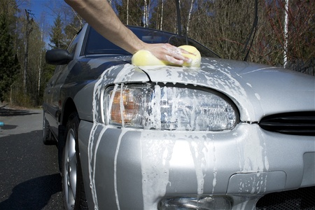 Man washing car on a sunny day with a sponge  Stock Photo
