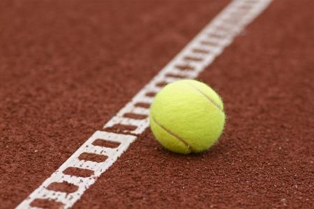 Closeup tennis ball laying on a clay tennis court