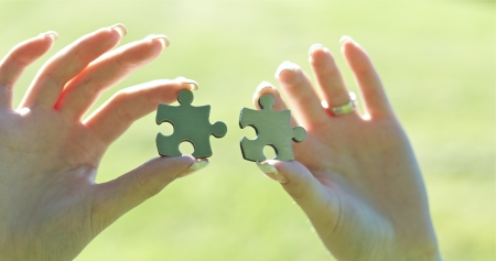 Woman holding two puzzle pieces with hands Stock Photo - 14414847