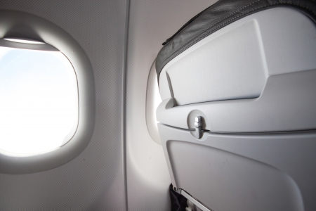 Airplane seat back and sun shining from window Stock Photo
