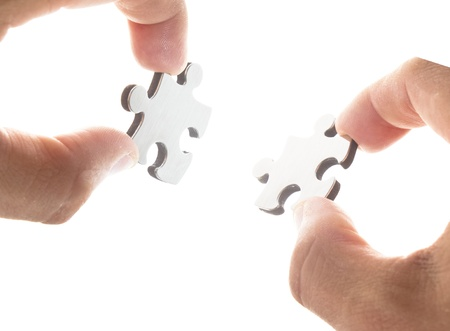 Holding two puzzle pieces for business connection metaphor