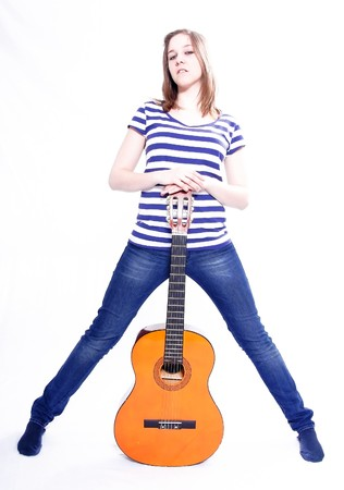 Studioshot of a young beautiful woman playing acoustic six-string guitar, isolated on white background