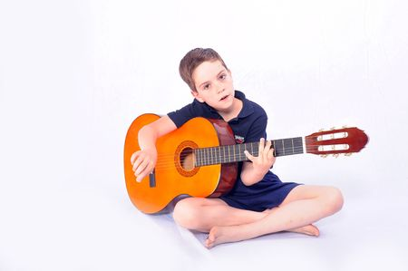 musicality: A studio shot of a young boy with an acoustic guitar, isolated on white background