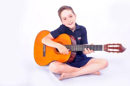 musicality: Un colpo di studio di un giovane ragazzo con una chitarra acustica, isolato su sfondo bianco  Archivio Fotografico