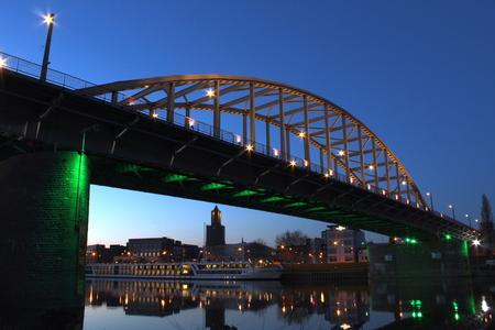 John Frost Bridge during blue hour in Arnhem, with a tourist boat on the river Rhine Foto de archivo