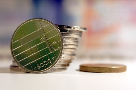 Dutch guilder coin with 10 and 25 guilder banknotes behind, and a reflection of a green 5 guilder banknote in the coin. Five guilder coin on the right. Stock Photo