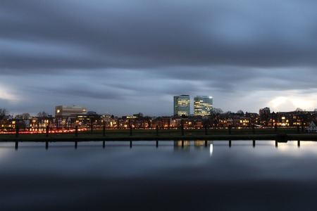 Skyline of the city of Arnhem in the Netherlands at sunset and a cloudy sky in January. Long exposure image.
