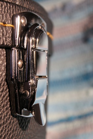 Lock of a guitar case, the steel metal lock is closed and locked Stock Photo