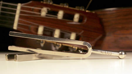 Tuning fork, two steel forks with classical guitars behind Stock Photo