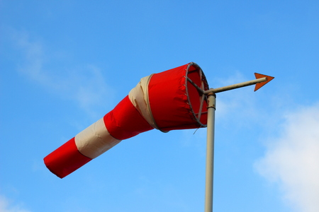 Windsock with a weather vane in front of a blue sky with white clouds. The windsock is red and white colored.