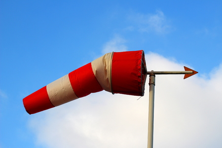 A red and white windsock with a weather vane in front of a blue sky with white clouds