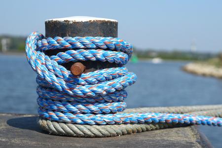 Blue rope around a bollard at a quay