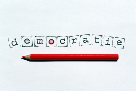 The Dutch word democracy written with stamps and ink on white paper