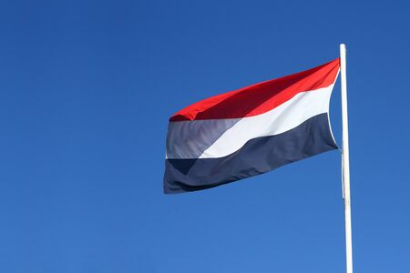 Dutch flag waving in the wind on a sunny day with a clear blue sky Фото со стока