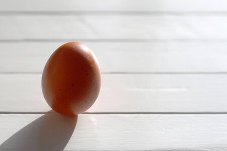 Chicken egg standing on an old white wooden table in the light of the sun