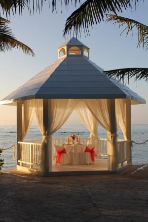 Um gazebo tropical praia no nascer do sol, definido e pronto para um pequeno-almo