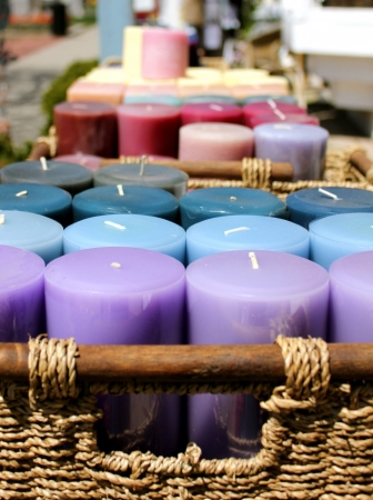 Rainbow coloured candles in wicker baskets for sale outside on the sidewalk in Niagara-on-the-Lake, Ontario, Canada Stock Photo